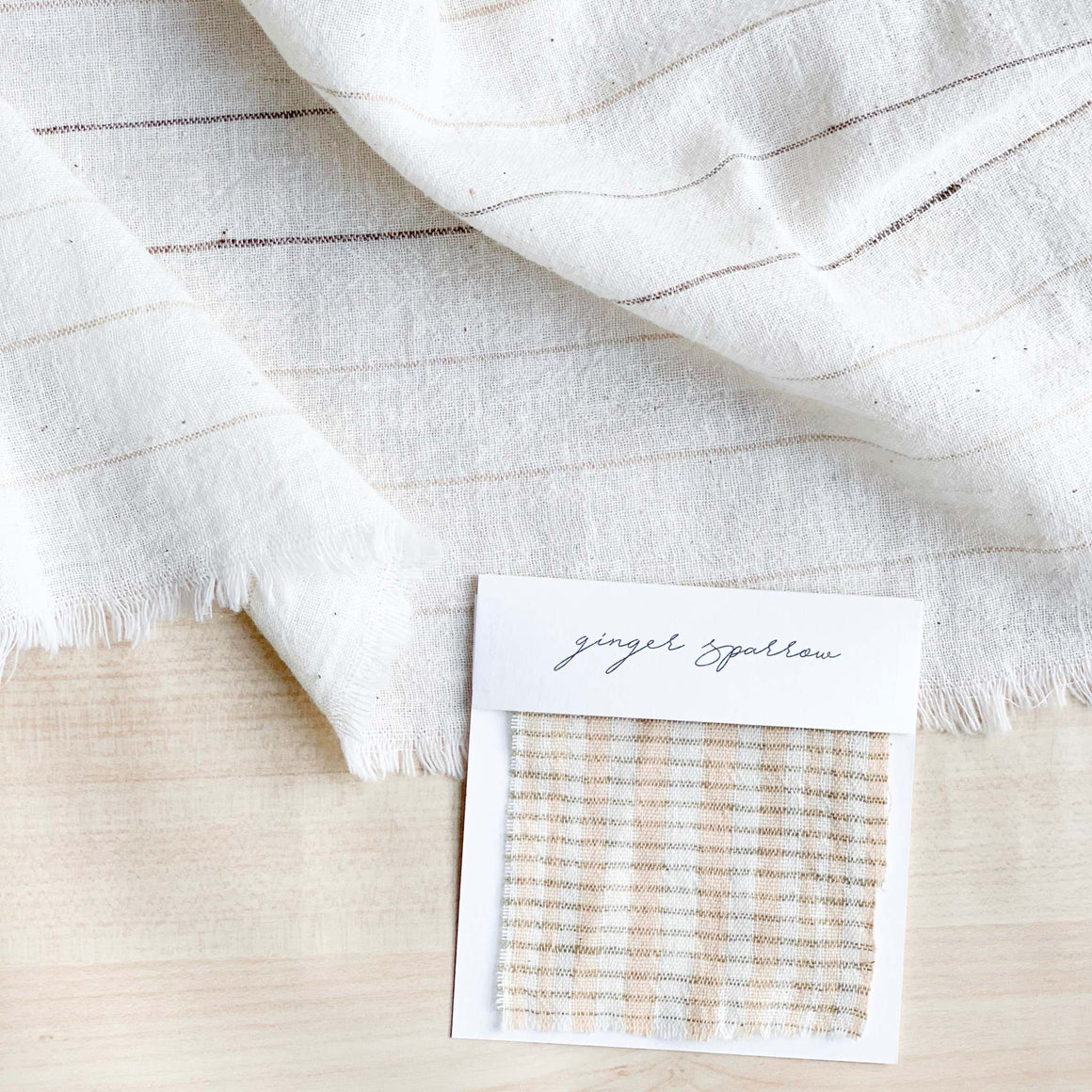 Handwoven Textile by Ginger Sparrow, a modern home decor brand. Featuring a light peach, gold and soft ivory checkered weave, it is light and airy, perfect for #throwpillows #drapes #livingroomdecor #bedroomideas