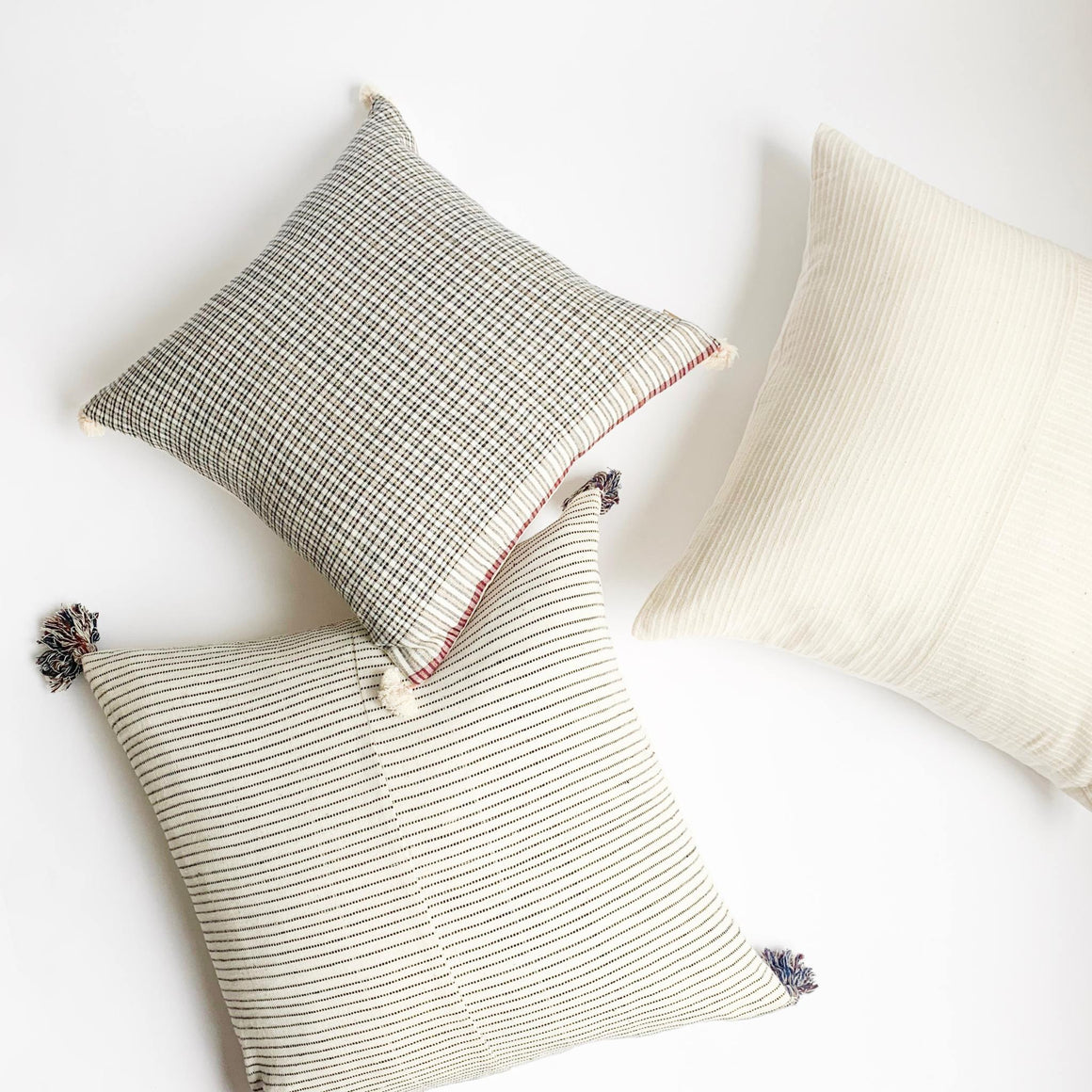 A soft ivory throw pillow in 22x22 inch size featuring ivory striped weave by Ginger Sparrow, a modern home decor brand with a  soul and a story.