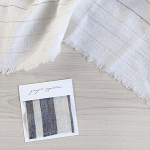 A soft ivory and charcoal striped handwoven cotton pillow . Handcrafted by Ginger Sparrow, a modern home decor brand.
