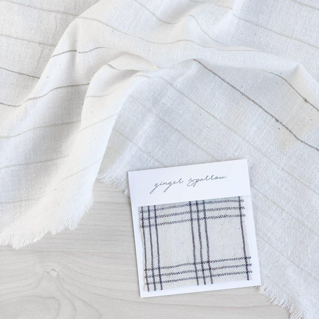 Handwoven Textile by Ginger Sparrow, a modern home decor brand. Featuring a charcoal black plaid pattern woven on a soft ivory ground. Light and airy its perfect for #throwpillows #drapes #livingroomdecor #bedroomideas