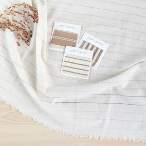 Handwoven Textile by Ginger Sparrow, a modern home decor brand. Featuring a brown thick stripe woven on a soft ivory ground. Light and airy its perfect for #throwpillows #drapes #livingroomdecor #bedroomideas