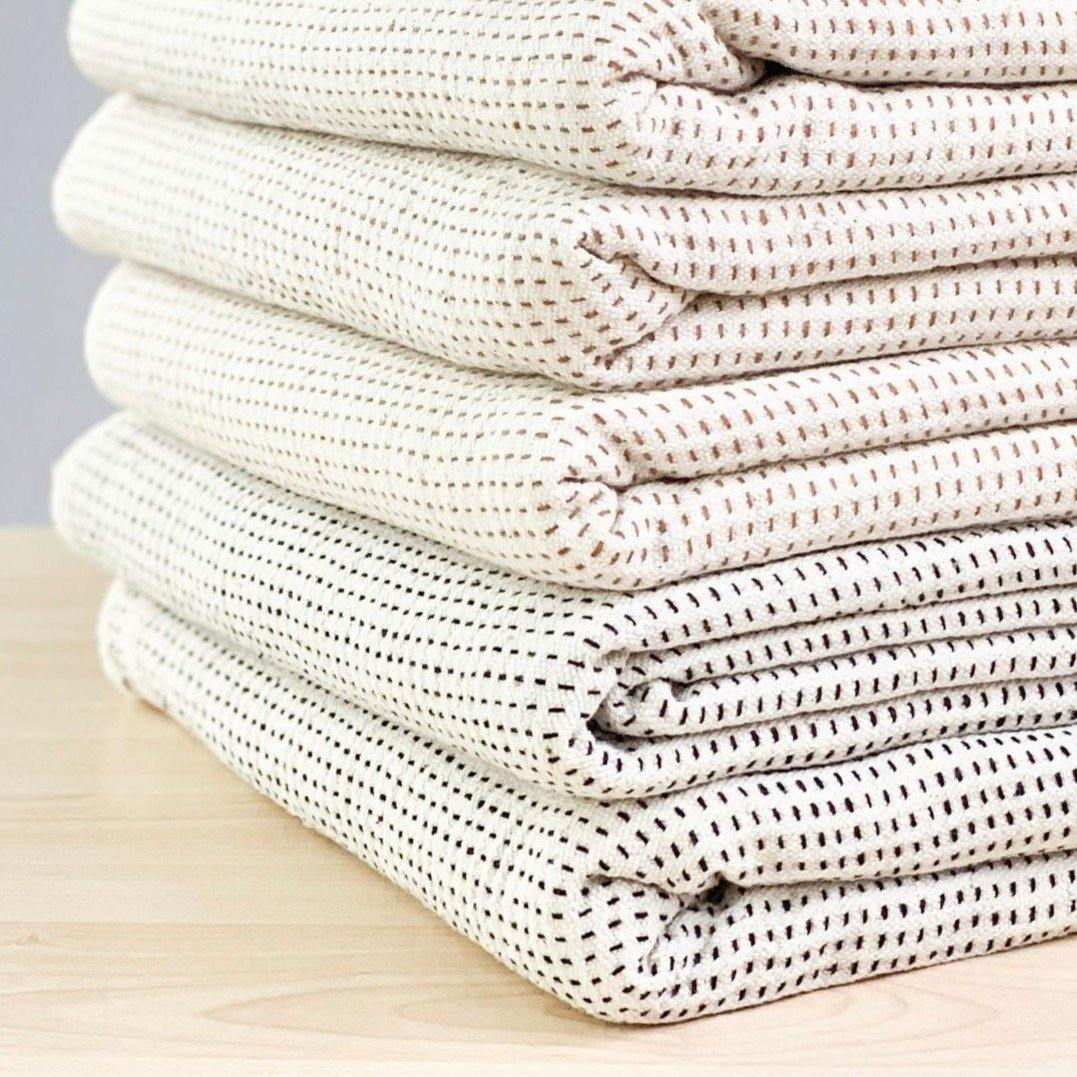 A soft ivory and brown striped handwoven cotton pillow . Handcrafted by Ginger Sparrow, a modern home decor brand.