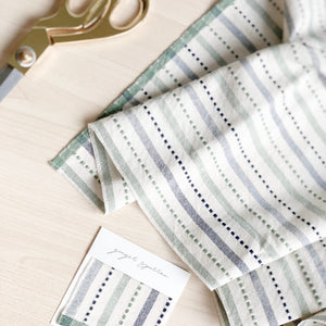 Handwoven Textile by the yard, crafted by Ginger Sparrow, a modern home decor brand. Featuring a soft ivory ground with a green and indigo striped weave. Light and airy its perfect for #windowshades #drapery #livingroomdecor #bedroomideas