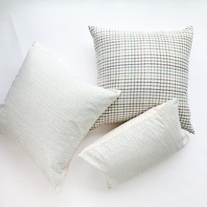 A soft ivory pillow featuring a green and indigo checkered weave. Handcrafted by Ginger Sparrow, a modern home decor brand.