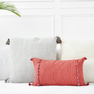 Throw pillows by Ginger Sparrow, a modern handcrafted home decor brand. A combination of ivory and earthy terracotta red pillows featuring a soft ivory base with ombre detail and finished with a row of fluffy marsala red cotton tassels for some extra lush. The second pillow is a terracotta red lumbar pillow finished with fluffy tassels along two edges.
