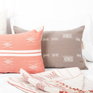 A coral accent pillow in 16x24 inch size featuring traditional Indian tribal motifs. Handcrafted by Ginger Sparrow, a modern home decor brand. Perfect for #livingroomdesign and #bedroomdecorideas