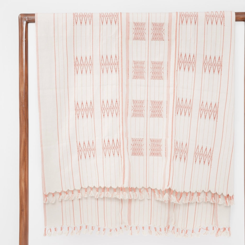 A soft ivory and coral throw or bed blanket in 42x72 inch size featuring traditional Indian tribal motifs. Handcrafted by Ginger Sparrow, a modern home decor brand. Perfect for #livingroomdesign and #bedroomdecorideas