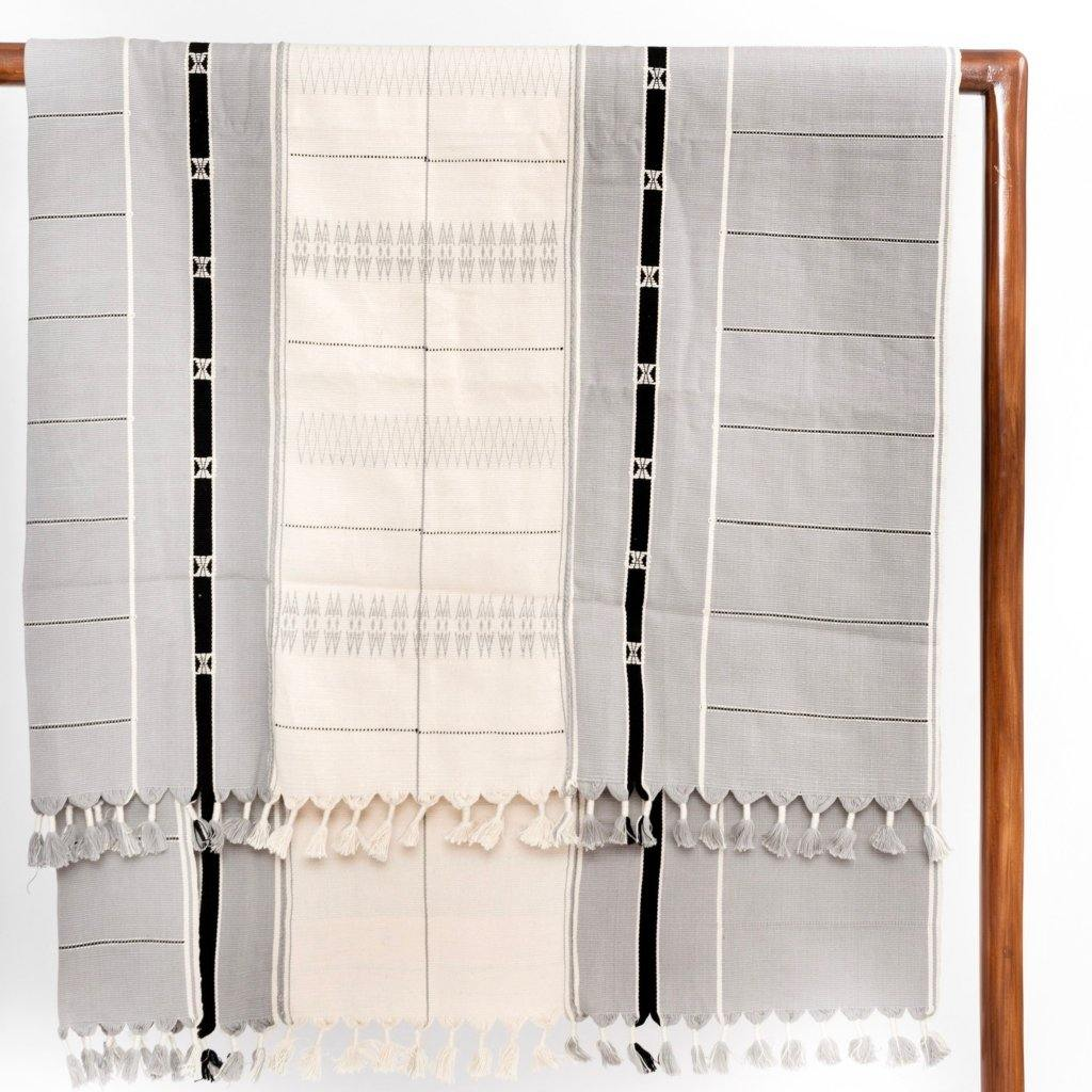 A soft ivory and silvery ash colored throw or bed blanket in 42x72 inch size featuring traditional Indian tribal motifs with subtle hints of black. Handcrafted by Ginger Sparrow, a modern home decor brand. Perfect for #livingroomdesign and #bedroomdecorideas