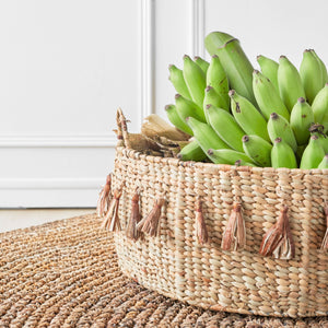 Buttery golden colored water grass floor basket finished with tassels and filled with raw bananas.