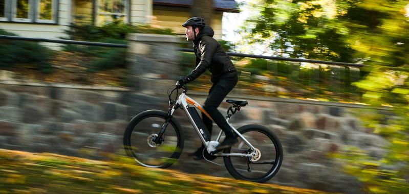 Riding a Juggernaut electric bike up an urban incline.
