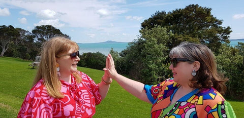 Image shows Louise and Carol high fiving each other outside.