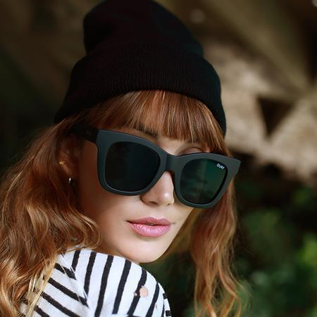 Model wearing Quay Ever After black sunglasses with beanie.