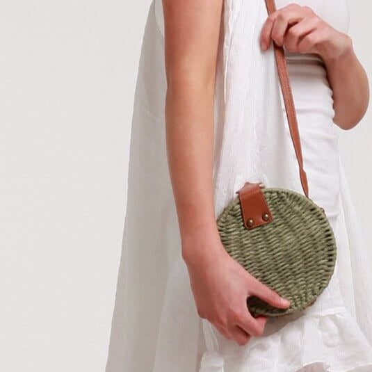 Woman wearing Aria green round bag