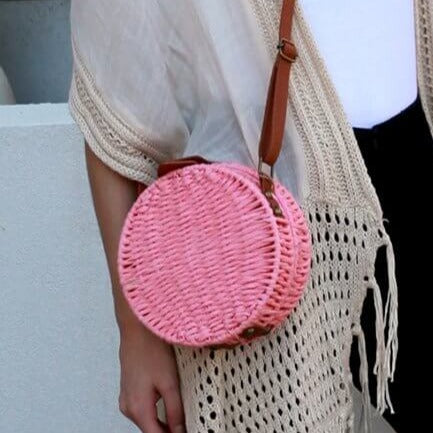 Woman wearing round Aria bag in pink