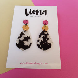 Pink, gold and panda dangles on white background.