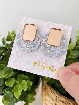 Image shows the glitter pop studs on a Elka Pretties earrrings card. The base is a round shattered silver and on top is a gold mirror square.