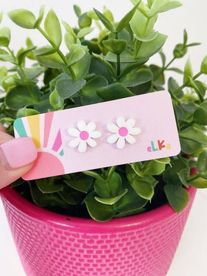 Image shows the white daisy mini studs with pink centres on a Elka earrings card. THe earrings are been held over a plant pot that is pink and has a green leafy plant inside.