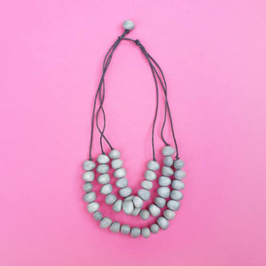 Dino beads necklace with three strands in light grey on a pink background.