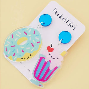 Image shows the the shake and donut on a Dented Diva earring card. The earrings have two drops, one is blue mirror and a donut sprinkles and the other earring is a shake with ice cream and a cherry on top.