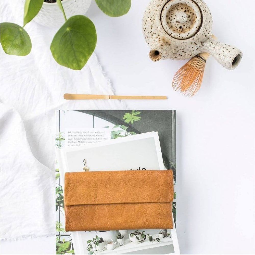 Beautiful flat lay with the Chloe tan leather wallet with white background and a touch of green.