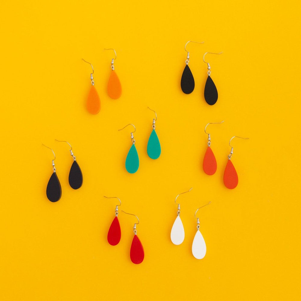 Flat lay of Everyday Droplet earrings in seven colours.