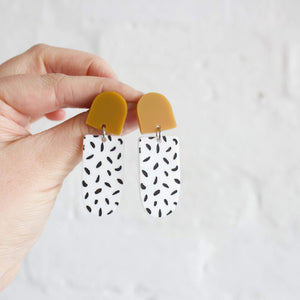 Statement earrings two drops, in mustard and white with black spots.