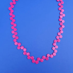 Happy pills necklace are wooden flat beads in fuchsia.