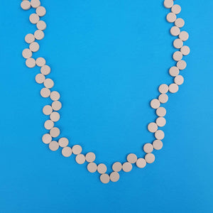 The Happy Pills necklace is made from wooden flat wooden beads in grey.