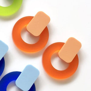 Close up of the Jelly Circle studs in Tangerine and Orange. The picture also has a partial view of the blue and green studs.