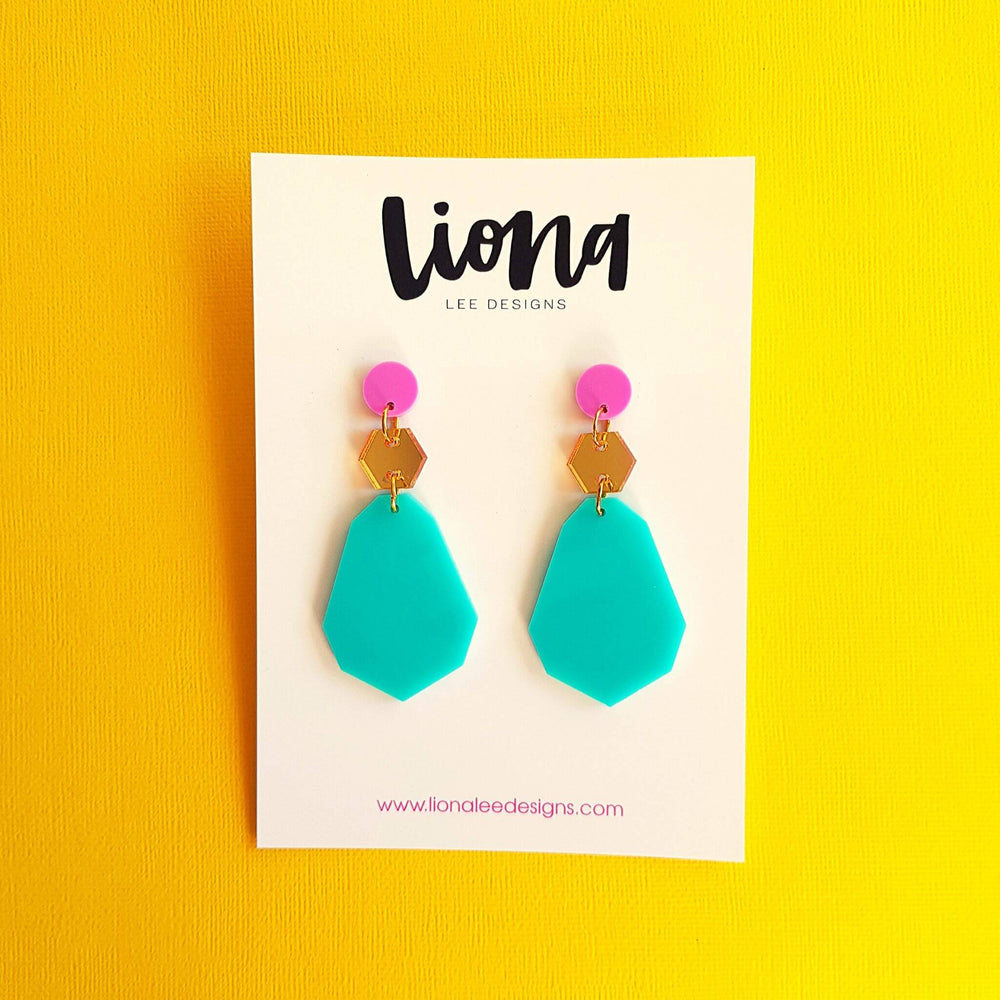 Purple, gold and aqua earrings on white background.