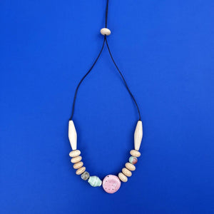 Mentos Natural necklace on a blue background.