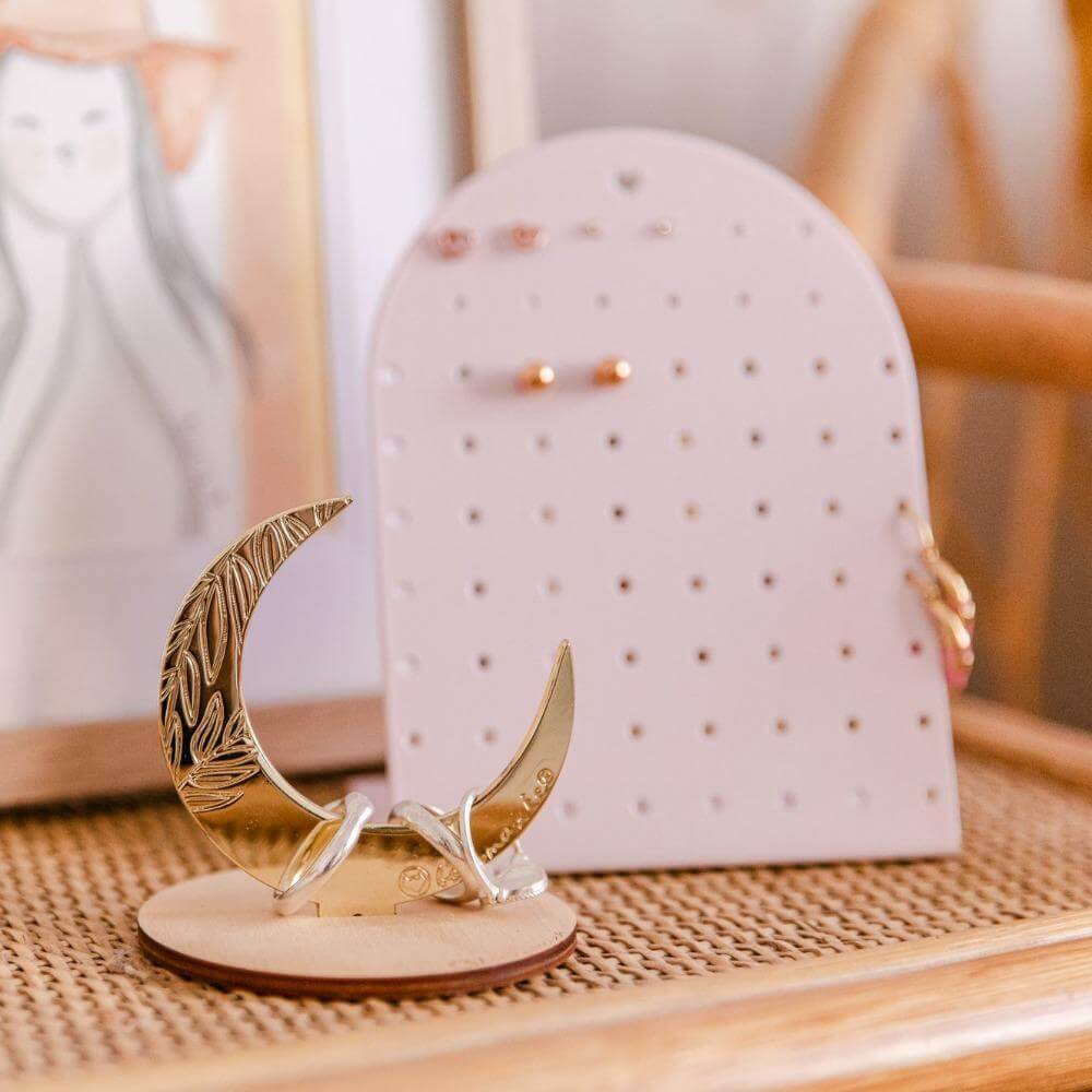 Image shows the mini earring holder on a bedside table with a crescent moon ring holder and a small hand drawn picture behind.