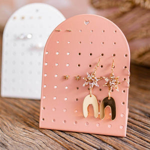 Image shows the mini earring holder in clay on a wooden surface. It has a mixture of earrings displayed.