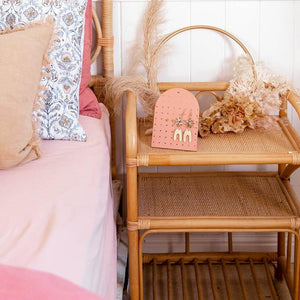 Image shows a wooden bedside table with dried flowers and the mini earring holder in clay on it with earring displayed.