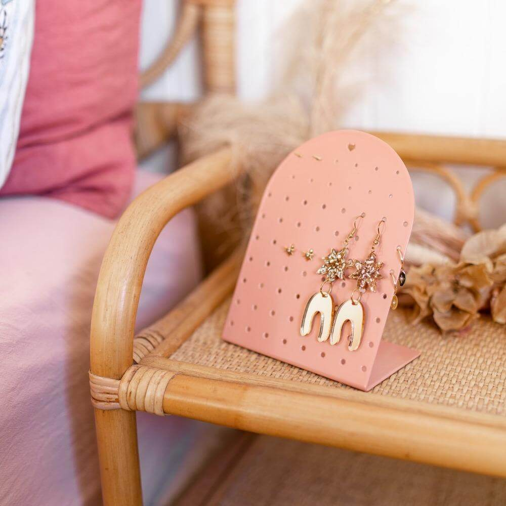 Image shows the clay mini earring holder stand on a bedside table with dried flowers behind it.