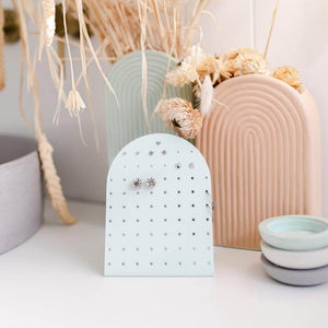 Image shows a styled photo of the mini earring holder stand in white on a white bench with a blush and mint rainbow vase behind it with dried flowers.