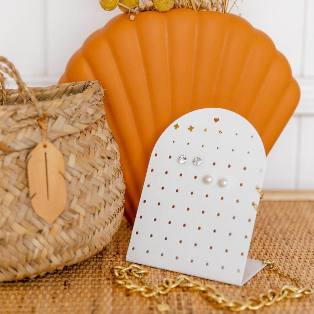 The white mini earring holder is styled in this photo with a orange fan shaped vase behind it and a weaved basket.