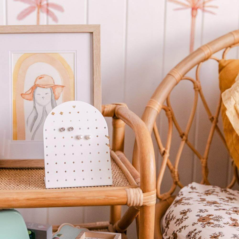 Image shows the white mini earring holder stand on a beside table next to a bed with a print behind it.