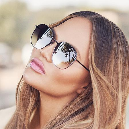 Model with sunnies on, close up with head tilted backwards.
