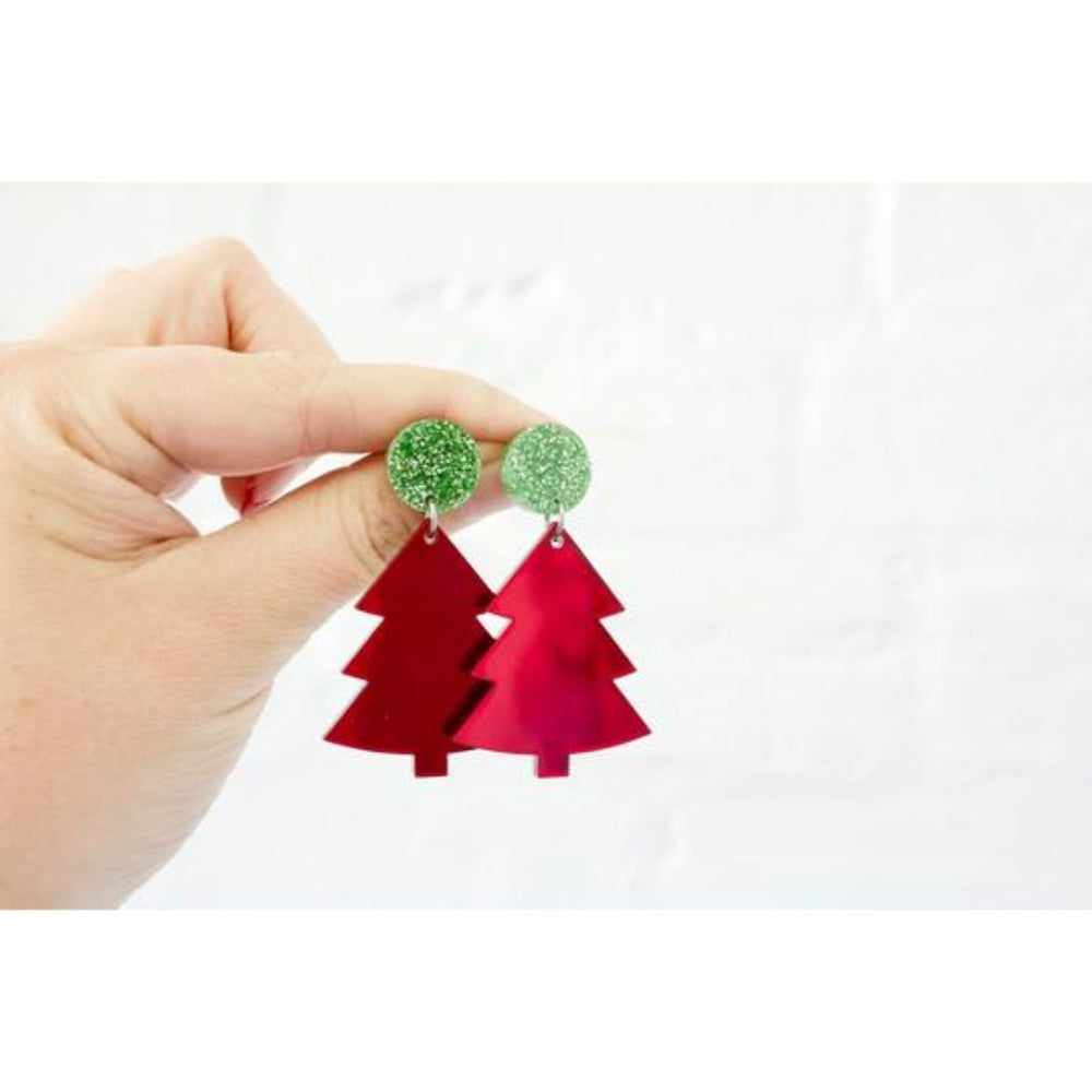Hand holding Christmas Tree earring coloured green and red on a white background.