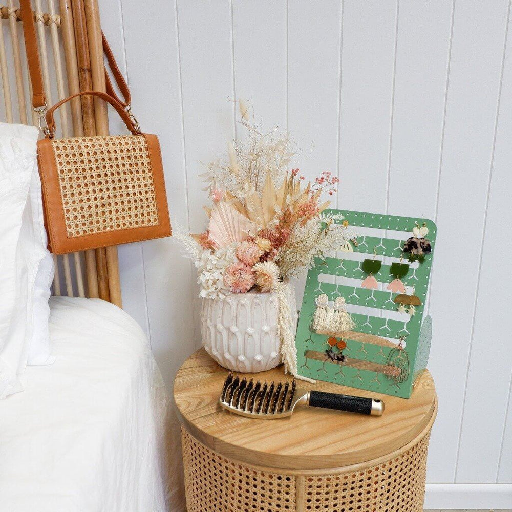 The Bon Maxie sage earring holder sitting on a wooden round bedside table next to a vase.