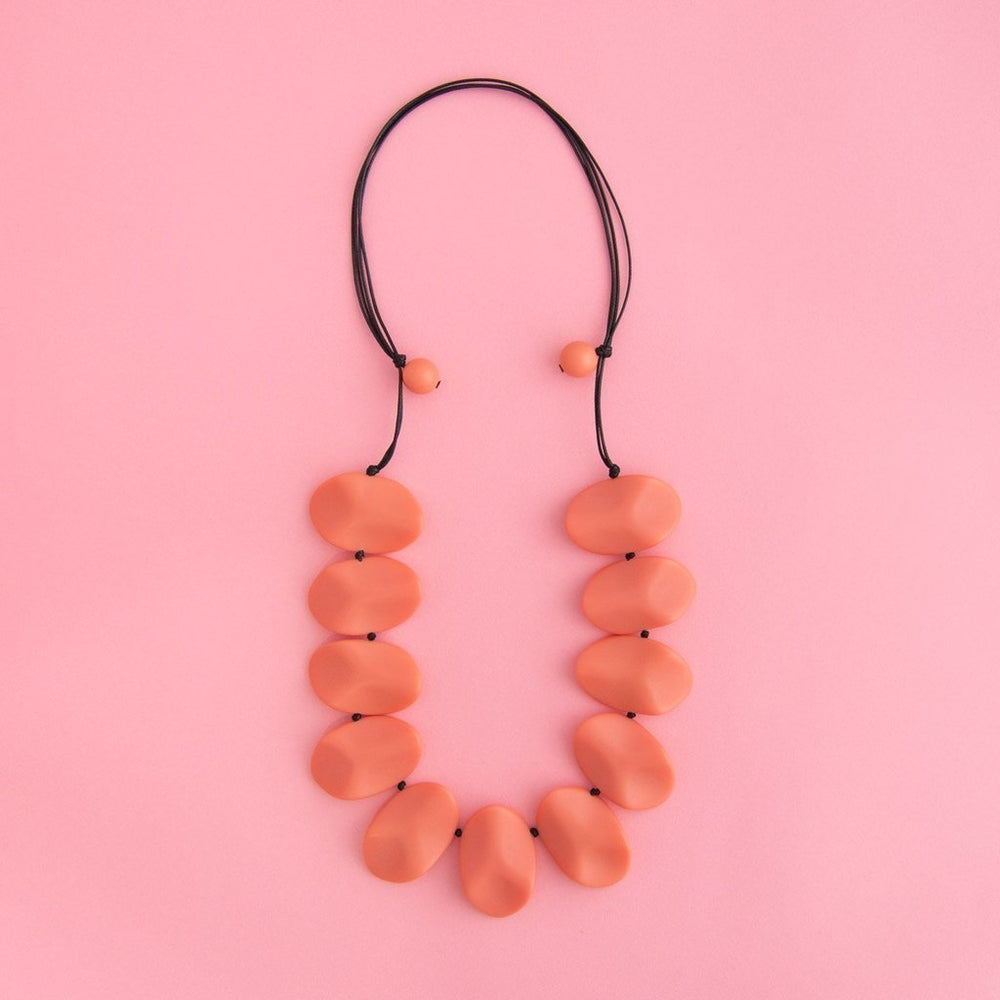 Simple Mayhem Everyday Necklace Blush on pink background.