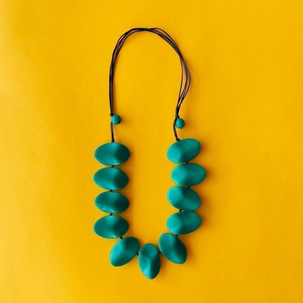 Simple Mayhem Everyday Wave Necklace Teal on yellow background.