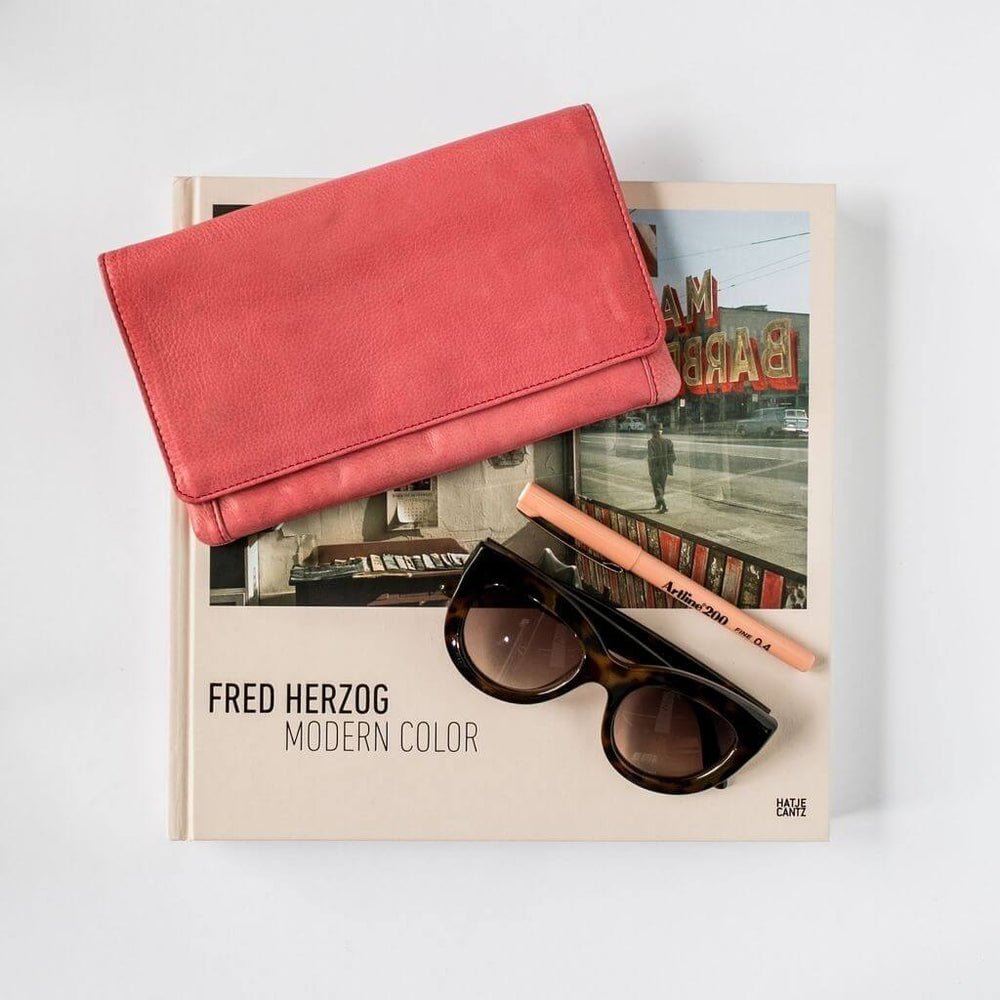 Flat lay of the Sirena leather purse on top of a book with sunglasses and a pen.