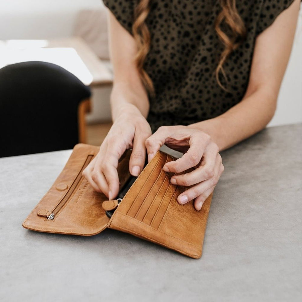 Woman opening the Sirena tan leather wallet.
