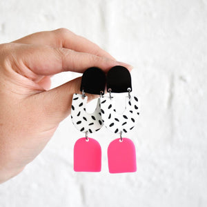 The Teagan earrings have three drops, first one is black, second is a u shape and is white with black spots and third drop is hot pink