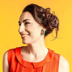 Model wearing watermelon earrings on yellow background.