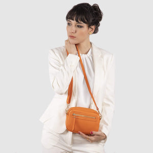 Woman holding Bonney Orange bag