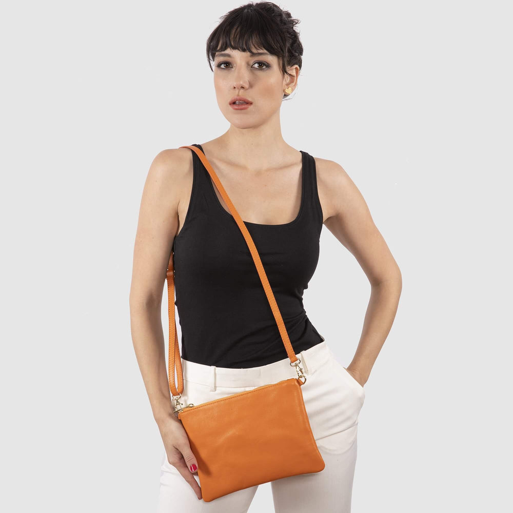 Model wearing the orange leather Tully as a crossbody.