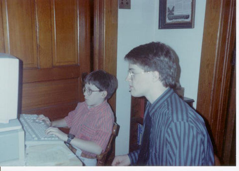 2 boys sitting in front of a computer playing a game